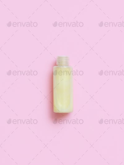 Reusable bottle with yellow liquid substance on pink background
