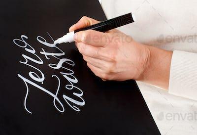 Woman writing on a small chalkboard zero waste lettering