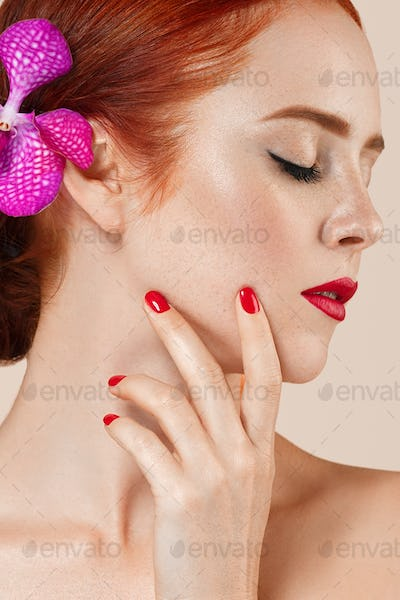 Beautiful woman portrait with flower in hair. perfect make manicure red lips nails. Beige background