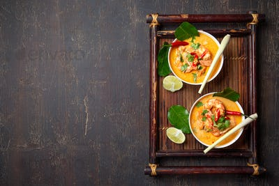 Shrimps Tom Yam Kung in white bowls on autentic thai tray top view, wooden background.