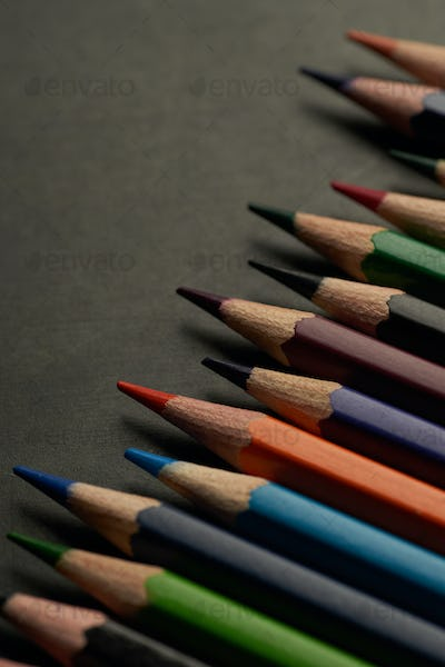 The large group of colored pencils on the black floor