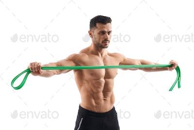 Shirtless bodybuilder holding resistance band