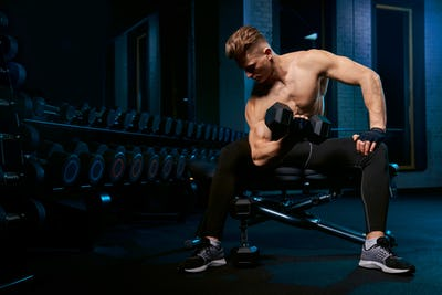 Muscular sportsman building biceps with dumbbell