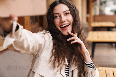 Image of happy woman taking selfie photo on cellphone and smiling