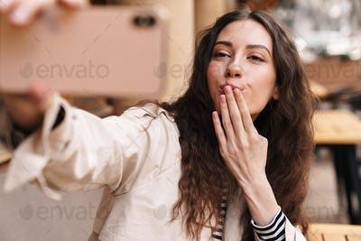 Image of happy woman taking selfie on cellphone and blowing air kiss