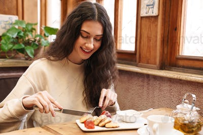 Image of woman smiling and eating pancakes while sitting in cozy cafe
