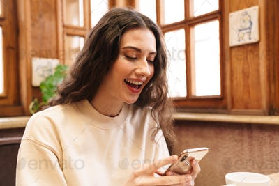 Image of woman smiling and using cellphone while sitting in cafe