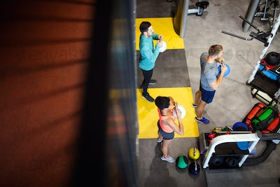 Young sporty people working out together with kettle bells in a gym