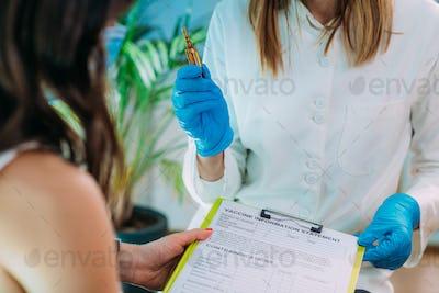 Female Patient Filling in Vaccine Information Statement. Corona Virus Vaccination.
