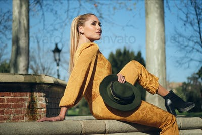 Young beautiful stylish woman in orange overalls with hat confidently posing on camera