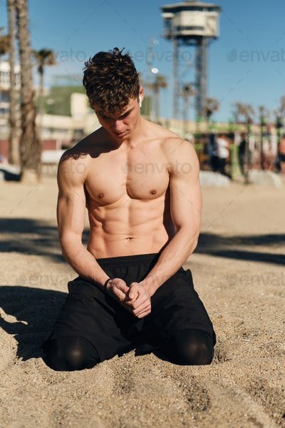 Handsome sporty guy with naked torso resting on sand after workout on hot summer day on beach