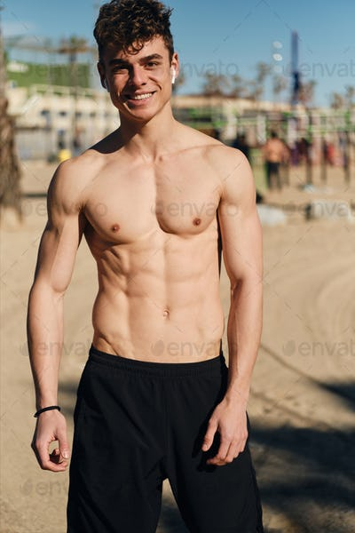 Young cheerful man with naked torso happily looking in camera after workout outdoor