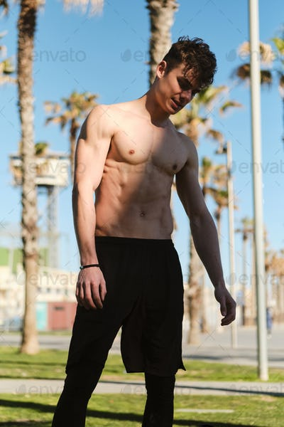 Attractive sporty guy resting after morning run along beach. Young attractive man on workout outdoor