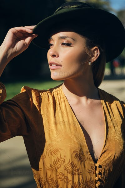 Side view of beautiful woman wearing hat and confidently looking away. Gorgeous model posing outdoor