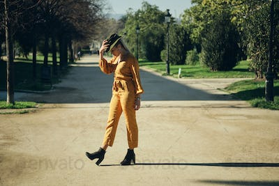 Young gorgeous woman in bright overalls and hat walking along park. Posh model posing outdoor
