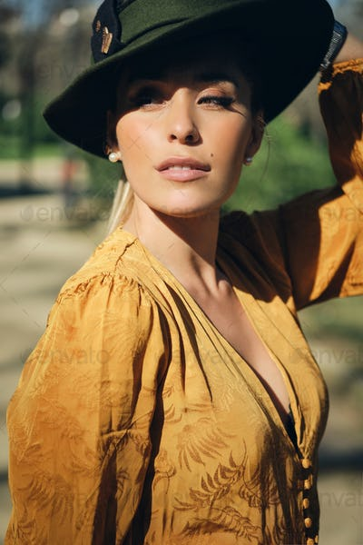 Portrait of young gorgeous woman wearing hat and confidently looking away