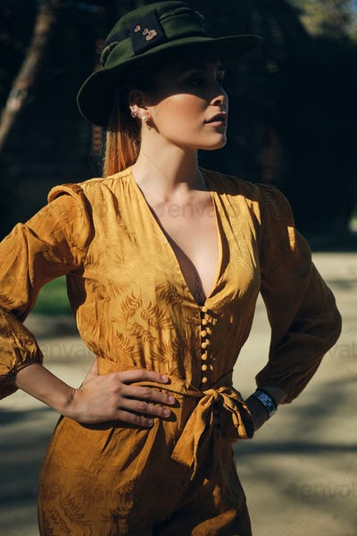 Young posh woman in overalls wearing hat confidently looking away. Gorgeous lady posing outdoor