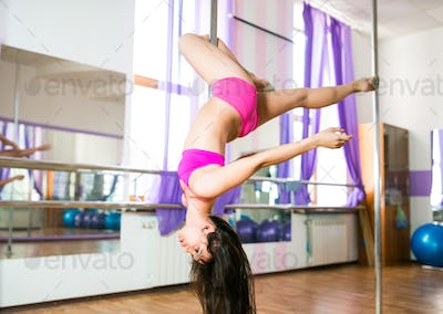Young brunette woman hanging and making dance poses on pylon