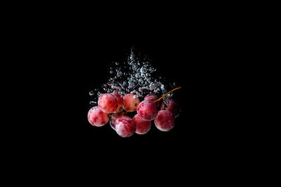 Red grapes sinking in water on black background with air bubbles