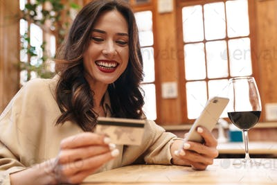 Image of excited adult woman holding credit card and using cellphone