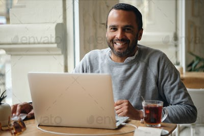 Adult cheerful businessman in sweater happily looking in camera working on laptop in cafe