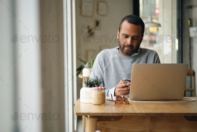 Adult businessman in sweater intently using smartphone while working on laptop in cafe