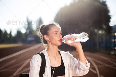 Portrait of beautiful girl in earphones drinking water on running track of stadium