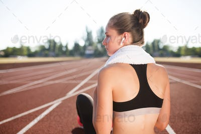 Sporty girl in wireless earphones with towel on neck looking aside from back on racetrack of stadium