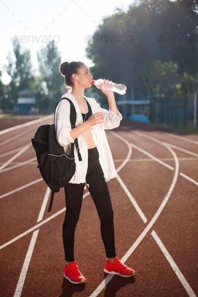 Girl in sporty top and legging with backpack on shoulder drinking pure water on racetrack of stadium