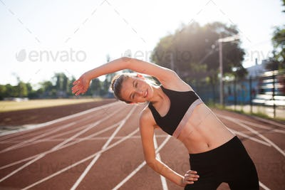 Smiling girl in sport top and leggings joyfully looking in camera stretching on treadmill of stadium