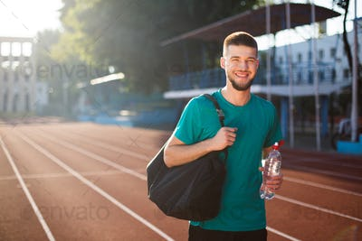 Young smiling man happily looking in camera with sport bag and bottle on running track of stadium