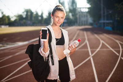 Pretty girl in earphones joyfully showing new cellphone on camera on treadmill of stadium