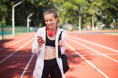 Pretty girl with headphones happily using cellphone with backpack on racetrack of stadium