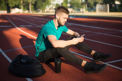 Young guy thoughtfully using cellphone spending time on running track of stadium