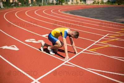 Young professional sportsman in starting position ready for running  on treadmill of stadium