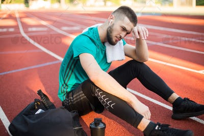 Young man with earphones tiredly looking aside with towel on shoulder on running track at stadium