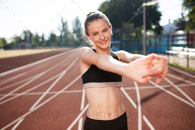 Pretty smiling girl with earphones in sport top happily looking in camera stretching on stadium
