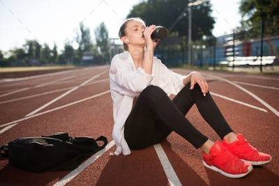 Beautiful girl in wireless earphones drinking pure water spending time on running track of stadium