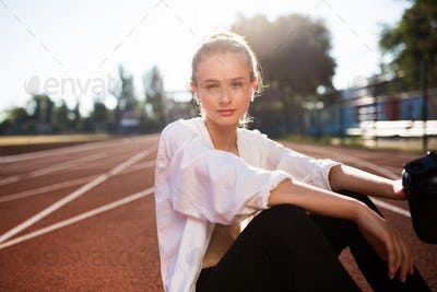 Beautiful sporty girl in wireless earphones dreamily looking in camera on running track of stadium