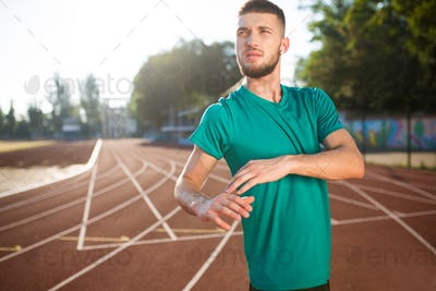 Young guy in wireless earphones thoughtfully looking aside spending time on treadmill of stadium