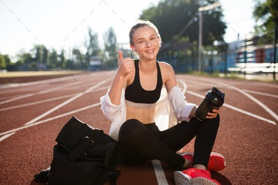 Smiling girl with earphones and bottle joyfully looking in camera showing thumb up on stadium