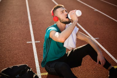 Young man in red headphones and sport wear drinking water from sport bottle on treadmill of stadium