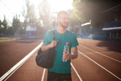 Young smiling sportsman joyfully looking aside with bottle of water on running track of stadium