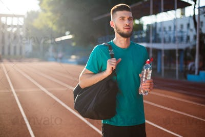 Young guy thoughtfully looking aside with sport bag and bottle of water on stadium