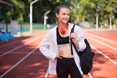 Beautiful smiling girl with headphones happily looking aside on racetrack of stadium