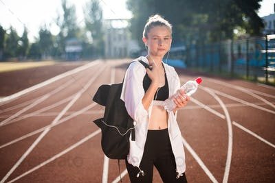 Pretty girl in sportswear dreamily looking in camera with backpack and bottle on running track