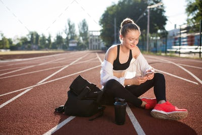 Smiling girl with wireless earphones and backpack joyfully using smartphone on treadmill at stadium