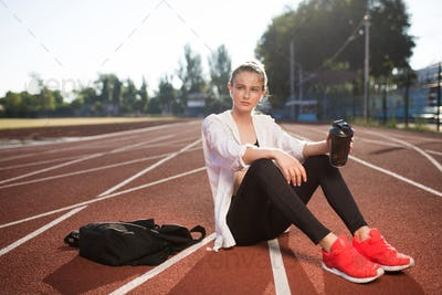 Attractive girl with earphones and sport bottle dreamily looking aside on running track at stadium