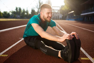 Young smiling guy in sportswear happily looking aside and stretching on treadmill of stadium