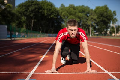 Concentrated sportsman thoughtfully looking forward in starting position ready to start running